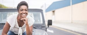 woman sitting on front bonnet of suv